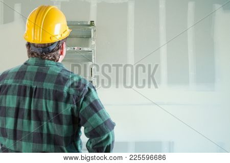 Contractor in Hard Hat Looking at Drywall.