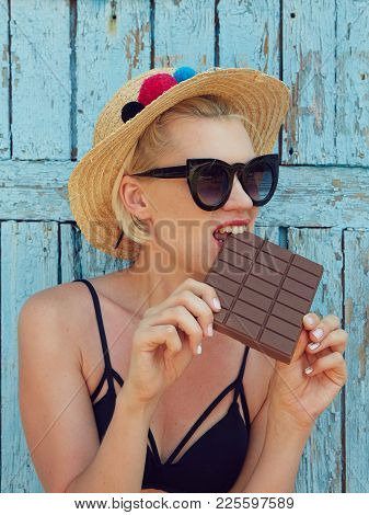 Young Attractive Woman In Sunglasses And In Straw Hat Eating Chocolate On A Blue Background. Film Ef