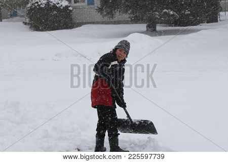 Lady Shoveling Snow During A Heavy Snow Fall.