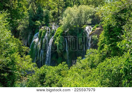 A Picturesque Waterfall Flows In A Dense Green Forest.
