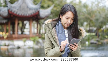 Young woman using mobile phone, sending sms and reply group chat on app at china, Chinese pavilion garden