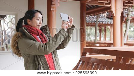 Asian woman visit chinese garden and using cellphone to taking photo and video