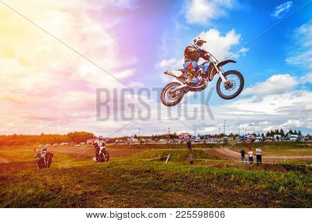 Racer On Motorcycle Participates In Motocross Cross-country In Flight, Jumps And Takes Off On Spring