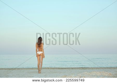 Beautiful Sexual Young Woman Stands On The Beach Against The Sea And Sky. Happy Woman Enjoying Summe