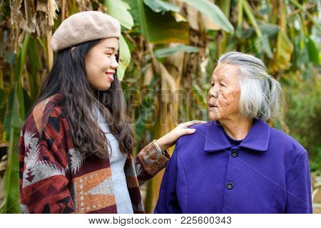 Asian Girl Spending Time Outdoors With Her Grandma In Green Tropical Environment