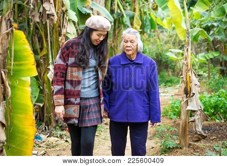 Asian Girl Having A Walk With Her Grandma In Green Tropical Environment
