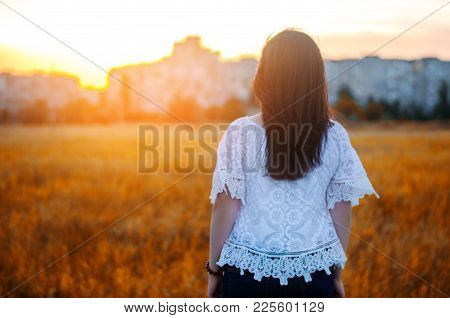 Young Woman Admires The Sunset  Back View.  Outdoor. Summer. View Of The City. Life Style