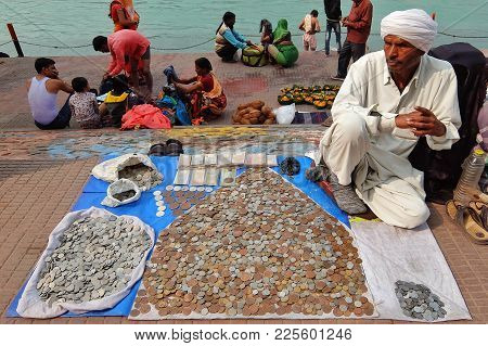 Haridwar, India - November, 6th, 2017. Man Selling Old Coins On The Riverbank Of Ganga River In Hari