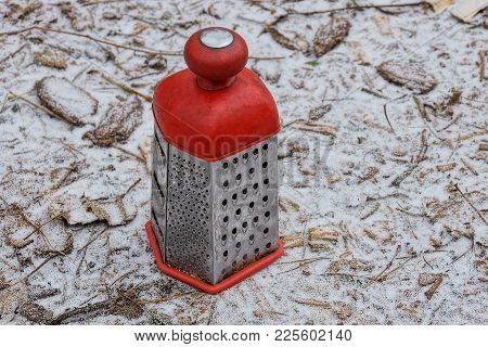 A Red-gray Big Grater Stands On The Ground In The Snow