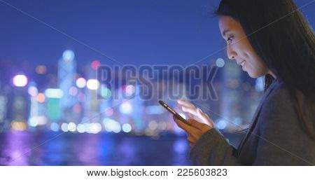 Businesswoman use of mobile phone in Hong Kong at night
