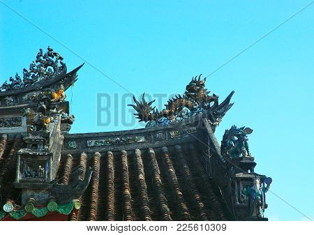 The Corner Of A Roof On A Vietnamese Temple Is Seen Against A Blue Sky. Dragons And Other Details Ar