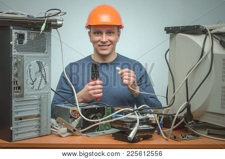 Happy Computer Network Technician Is Crimping A Network Cable By Crimper Tool In His Hands. Connect