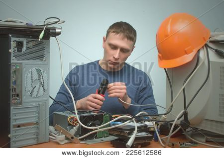 Serious Computer network technician is crimping a network cable by crimper tool in his hands. Connection of workstations to network. poster