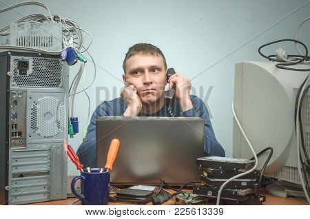 Tired And Bored Computer Repairman Is Sitting On His Workplace And Consulting A Users By A Phone. Co