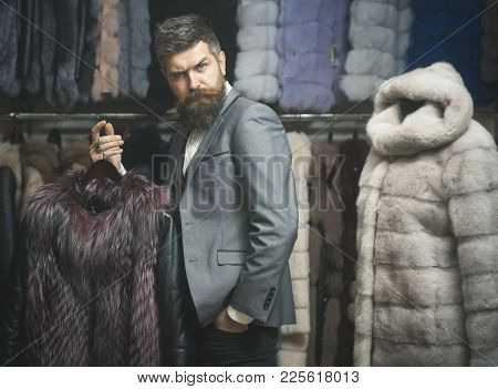 Man With Beard And Mustache Holds Fur Coat. Winter Clothing Concept. Guy Holds Furry Coat In Shop Wi