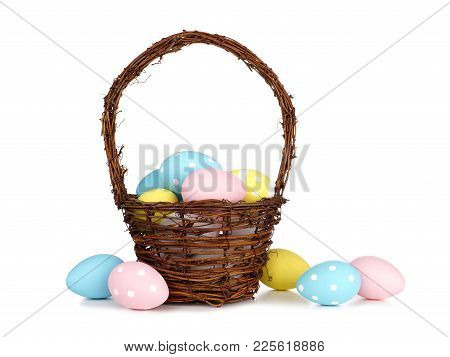 Easter Basket Filled With Colorful Hand Painted Blue, Pink And Yellow Easter Eggs Over A White Backg