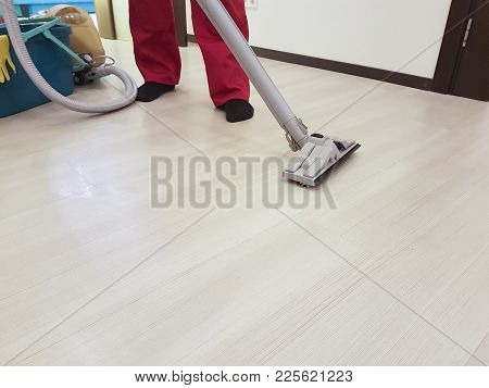 The Employee Of The Firm Removes Dirt From The Floor With A Steam Vacuum Cleaner In The Apartment