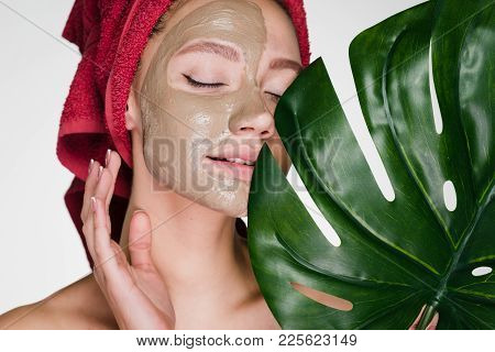 A Bewildered Woman With A Towel On Her Head Applied A Cleansing Mask On Her Face