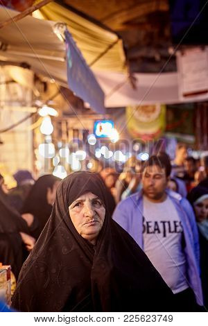 Tehran, Iran - April 27, 2017: An Elderly Muslim Woman In A Black Chador Stands In Front Of A Man In