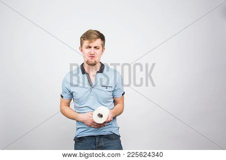 Young Man With Toilet Paper On The White Background - Health Problem Concept.