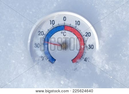 Thermometer with celsius scale placed in a fresh snow showing sub-zero temperature minus 26 degree - frosty winter weather concept
