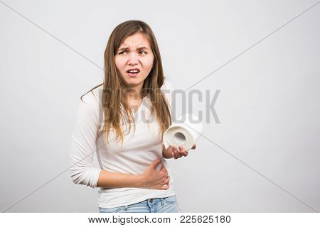 Young Woman With Toilet Paper On The White Background - Health Problem Concept.