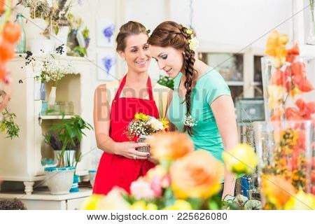 Women in flower store enjoying the roses sniffing at them