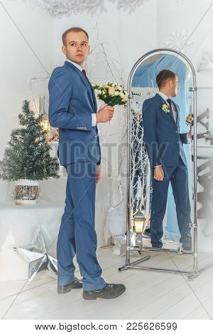 Portrait Handsome Groom In A Blue Suit Near Mirror In The Studio During A Photoshoot