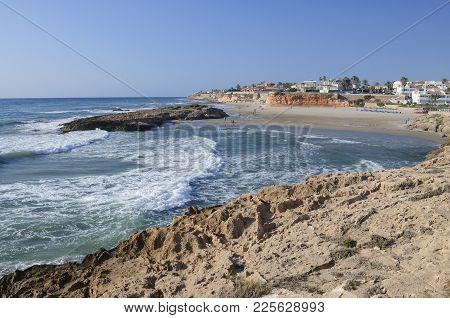 Costa Blanca, Spain - July 24, 2012: Cala Capitan Beach On A Windy Day On July 24, 2012 In La Zenia,