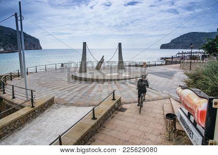 Camp De Mar, Mallorca, Spain On October 25, 2013: Bicyclist Races Downhill Near Sundial Sculpture By