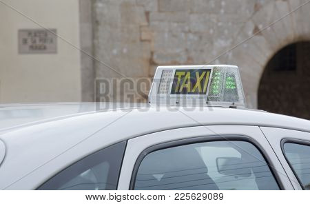 Santanyi, Mallorca, Spain On November 2, 2013: Taxi Top With Old Vaulted Stone Building In The Backg