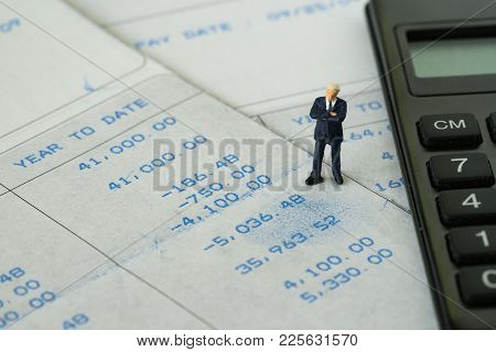 Office Salary Man Or Tax Calculation Concept, Miniature Figure Business Man Standing On Salary Slip