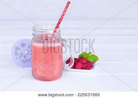 Raspberry Smoothie And Raspberry Fruit On White Wood Floor.