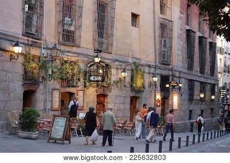 Passersby In Front Of The Meson Rincon De La Cava Tapas Restaurant Off Plaza Mayor - Madrid, Spain,