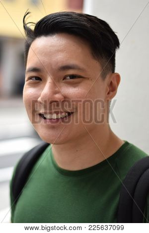 A Young Handsome Asian Chinese Man Smiling Happily Outdoor