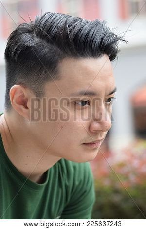 A Young Asian Handsome Chinese Man Looking Sad Outdoor