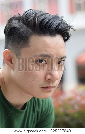 A Young Asian Handsome Chinese Man Looking Sad Staring At The Camera