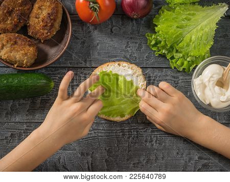 Girl Puts Lettuce On A Bun To Make A Hamburger. Cooking Hamburger For School Lunch Child.