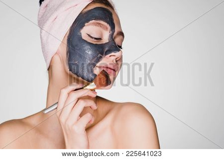 An Astonished Woman With A Towel On Her Head Applies A Cleansing Mask On Her Face