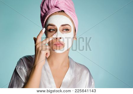 A Woman With A Towel On Her Head Applies A Cleansing Mask On Her Face