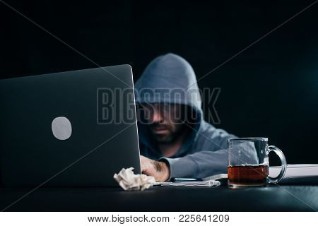 Man Hacker In A Jacket With A Hood That Prints Something In A Laptop