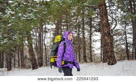 Portrait of Young Woman Hiking with Big Backpack in the Beautiful Winter Forest