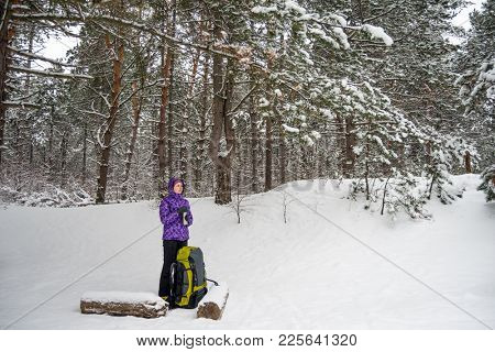 Woman Resting with Big Backpack in the Beautiful Winter Forest