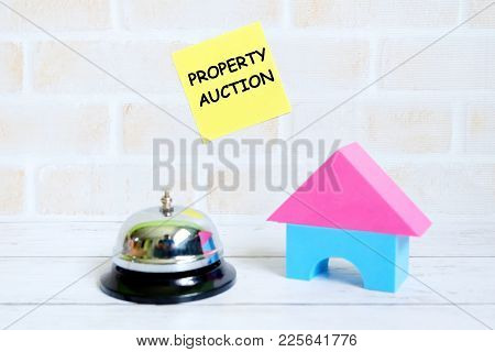 Selective Focus Of Yellow Sticky Notes Written With Property Auction With House Model And Ring Bell