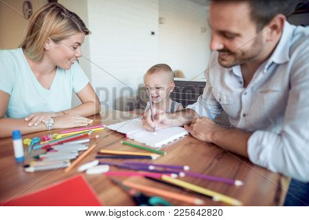 Young Parent And Son Drawing In The Living Room.