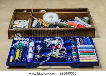 Garment Accessories Spread On A Light Wooden Table. Threads, Scissors And Sewing Needles In A Tailor