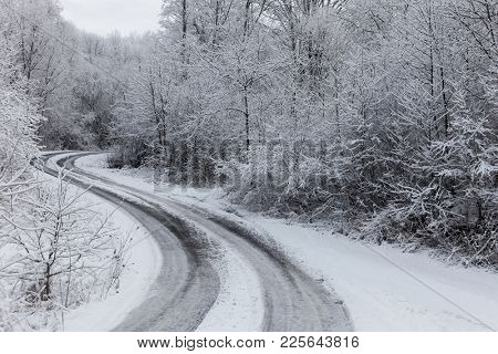 Winter road through icy forest covered in snow after ice storm and snowfall
