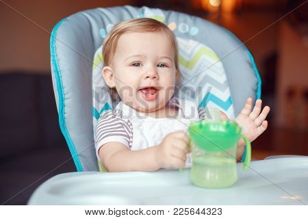 Portrait Of Cute Adorable Caucasian Child Kid Girl Sitting In High Chair Drinking Water From Spill-p