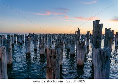 Old Wooden Pylons Of Destroyed Jetty, Pier At Dusk. Industry Background