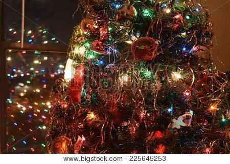 Christmas Tree Adorned With Decorations, Lights And Tinsel At Night With Reflection In The Window At